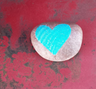 uncoated gray love-rock with aqua colored heart decoupage sitting on a red metal background with rust